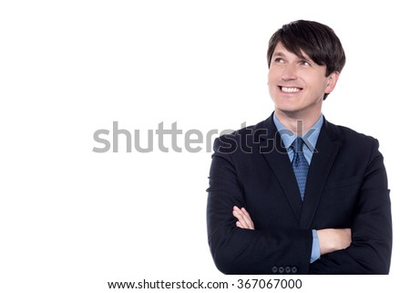 Pensive businessman looking up with folded arms - stock photo