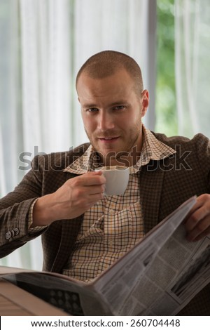 Pensive businessman reading a newspaper in cafe - stock photo