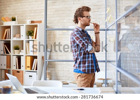 Pensive businessman reading reminders in office - stock photo