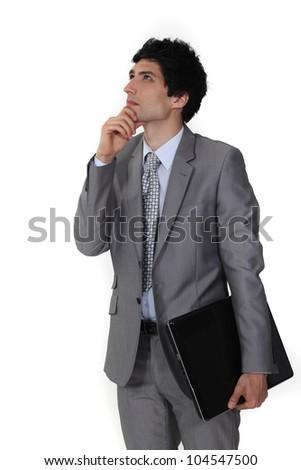 Pensive businessman rubbing his chin - stock photo