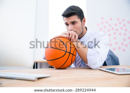 Pensive businessman sitting at the table with ball in office. Looking away
