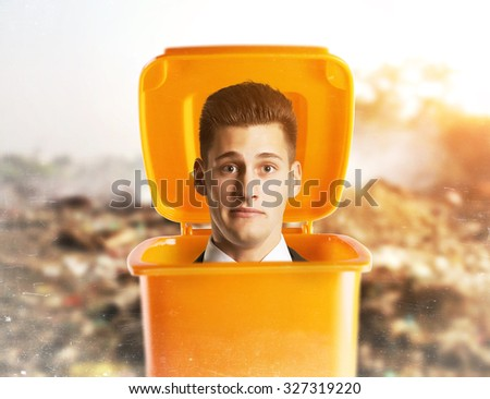 Pensive businessman standing inside a trash can - stock photo
