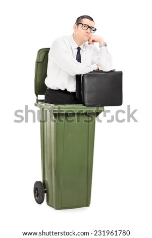 Pensive businessman standing inside a trash can isolated on white background - stock photo