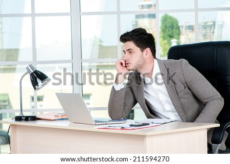 Pensive businessman. Successful confident businessman sitting in office at the table and working on a laptop while young businessman in formal attire thinking on the problem