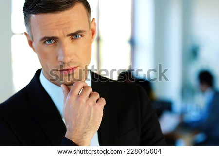 Pensive businessman with colleagues on background - stock photo