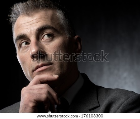 Pensive businessman with hand on chin on dark background.