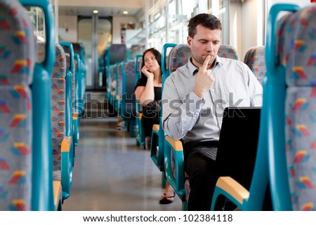 Pensive businessman working on the train - stock photo