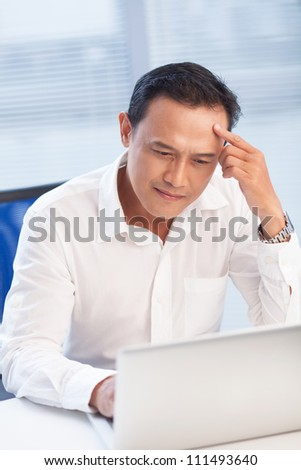 Pensive businessman working with laptop at the table - stock photo