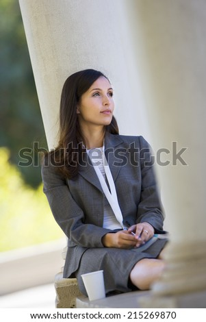 Pensive businesswoman, in grey suit, sitting alone on coffee break, daydreaming (tilt) - stock photo