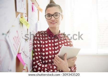 Pensive businesswoman posing with her digital tablet