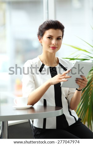 Pensive businesswoman reading an article on tablet computer in a cafe - stock photo