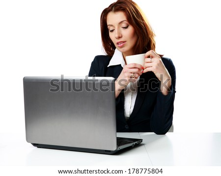 Pensive businesswoman sitting on the table with laptop and drinking coffee isolated on a white background