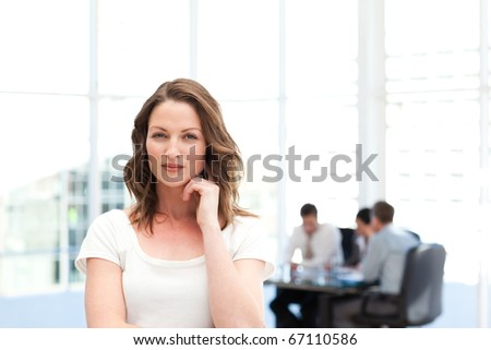 Pensive businesswoman standing in front of her team while working in the background