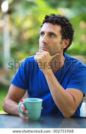 Pensive Caucasian adult sitting outdoors in Maui - stock photo