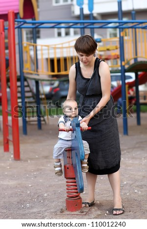 Pensive child is swinging on spring toy horse - stock photo