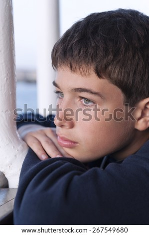 Pensive child looking through a window - stock photo
