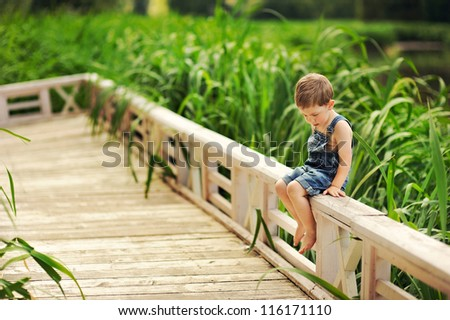 pensive child sits on the bank of the river in the long grass - stock photo