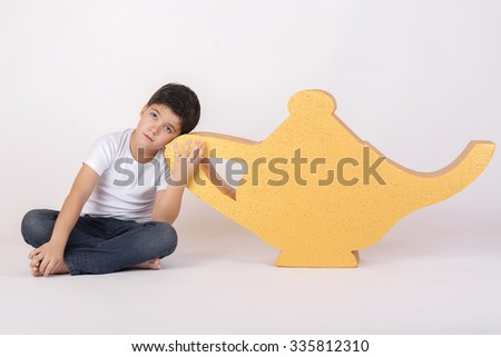 pensive child with a magic lamp - stock photo