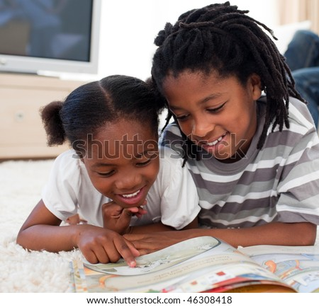Pensive children reading a book lying on the floor - stock photo