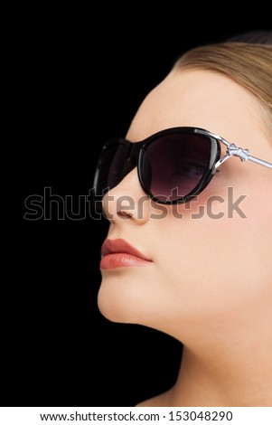 Pensive classy blonde on black background wearing sunglasses