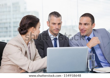Pensive colleagues working together on their laptop in bright office - stock photo