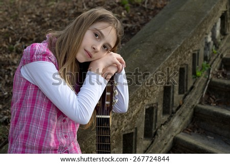 Pensive Cute Girl Leaning on Guitar and Looking at the Camera Against Old Stairs - stock photo