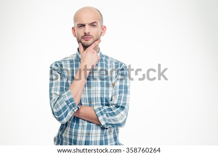 Pensive doubtful young man in checkered shirt holding hand on his chin over white background - stock photo
