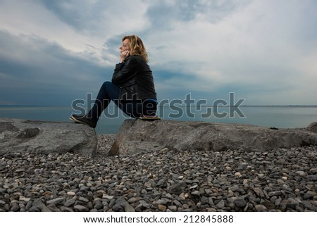 Pensive/dreaming woman on the beach - stock photo