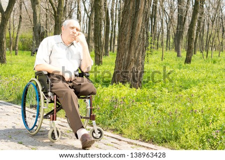 Pensive elderly amputee sitting alone on a rural pathway in his wheelchair with his chin resting on his hand staring into the distance - stock photo