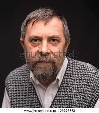Pensive elderly man on a dark background