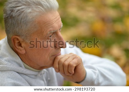 Pensive elderly man resting in a park in autumn - stock photo