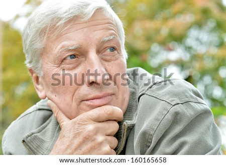 Pensive elderly man resting in a park in October - stock photo