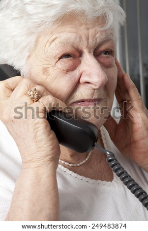pensive elderly woman calling on the phone