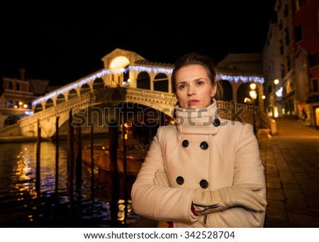 Pensive elegant young woman in white coat standing in front of Rialto Bridge in the evening. She having Christmas time trip and enjoying stunning views of Venice, Italy - stock photo