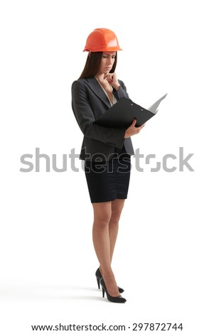 pensive engineer woman in orange hardhat reading documents in folder. isolated on white background - stock photo