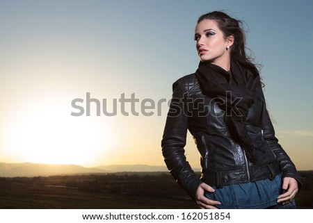 pensive fashion woman in leather jacket is looking away in the dusk