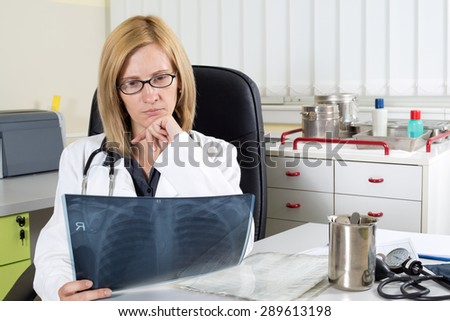 Pensive Female Doctor With Hand on Chin Looking at Patient's Lung X-ray in Consulting Room  - stock photo
