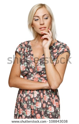 Pensive female in summer dress standing with folded hands looking down against white background
