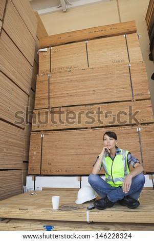 Pensive female industrial worker sitting cross-legged on wooden planks - stock photo