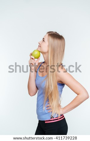 Pensive fitness woman holding apple isolated on a white background - stock photo
