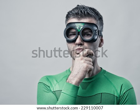 Pensive funny superhero with hand on chin looking at camera.