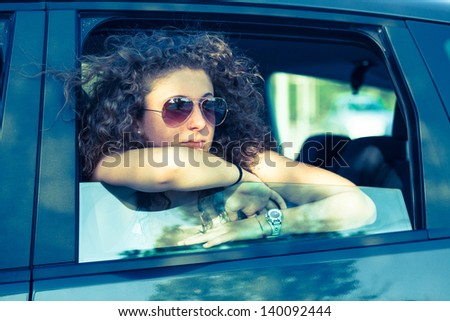 Pensive Girl Looking out of Car Window - stock photo