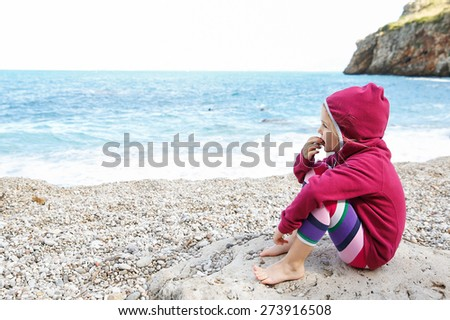 Pensive girl relaxing on a pebbly beach, eating and observing the sea after swimming, barefoot and dressed in leggings and fleece. Family and children on vacation, late summer concept.  - stock photo