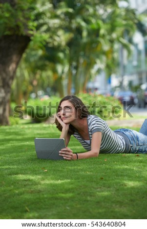 Pensive girl with tablet computer lying on grass in park