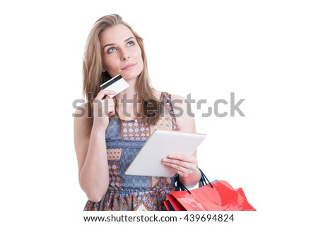 Pensive gorgeous lady with credit card and modern tablet thinking what to buy as internet shopping concept isolated on white studio background - stock photo