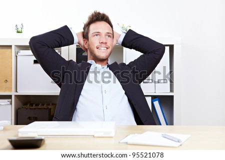 Pensive happy business man in office relaxing with hands behind his head - stock photo