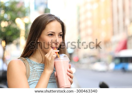 Pensive happy woman sipping a milkshake in the street  - stock photo