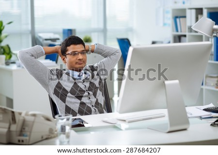 Pensive Indian programmer with hands behind his head looking at the screen