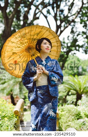 Pensive Japanese woman in traditional clothes walking around the garden - stock photo