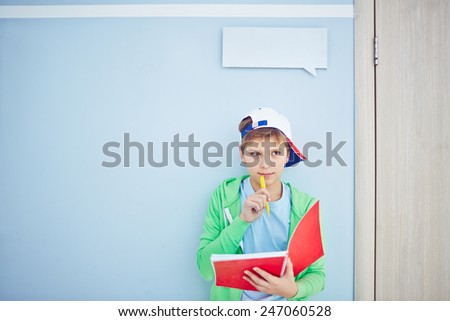 Pensive lad with exercise-book - stock photo